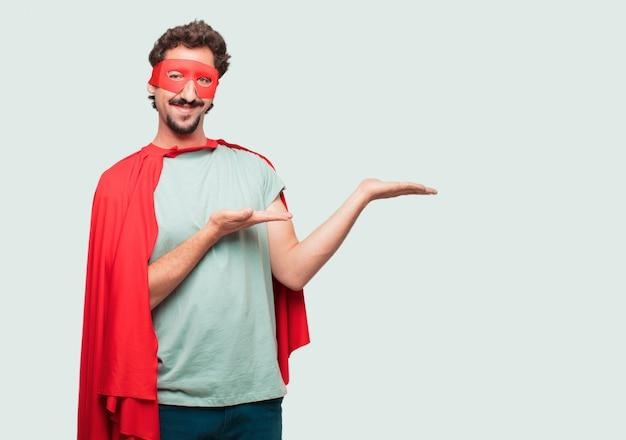 Сумасшедший человек, как супер герой, улыбающийся с удовлетворенным выражением, показывающим объект или концепцию