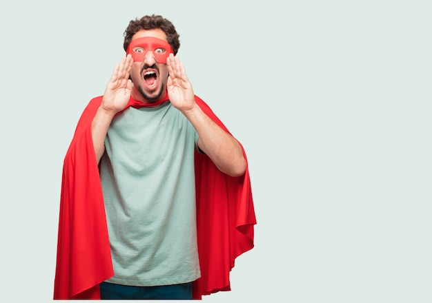 Crazy man as a super hero shouting loud like crazy, calling with hand with an angry expression