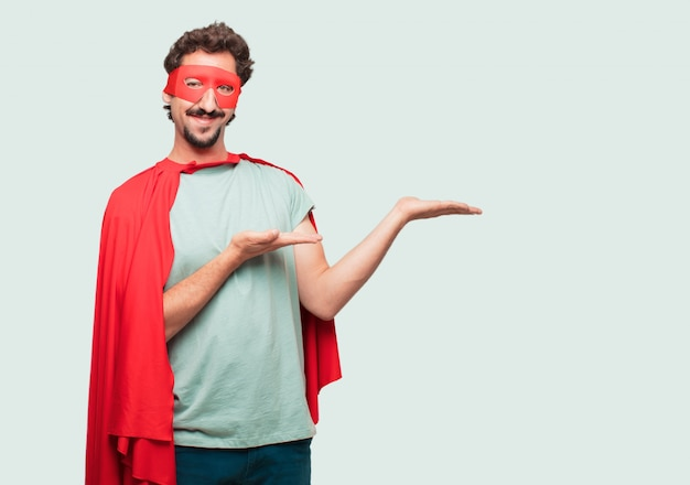 Crazy man as a super hero smiling with a satisfied expression showing an object or concept