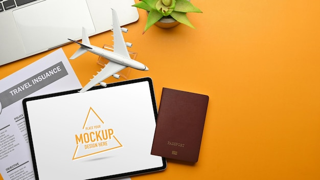 Creative flat lay workspace in travel concept with digital tablet passport travel insurance laptop