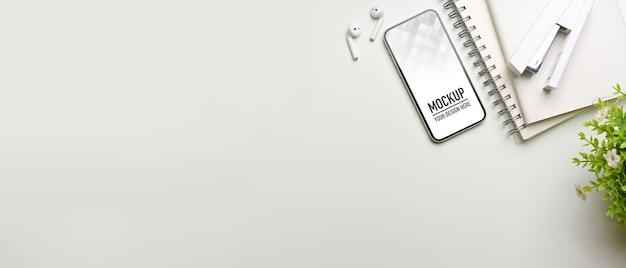 Креативное плоское рабочее пространство с макетом смартфона, канцелярскими принадлежностями и аксессуарами