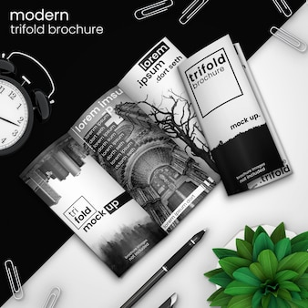 Creative, modern trifold brochure mockup of two trifold brochures on modern black and white design with alarm clock, paper clips, pen, and green plant, psd mock up