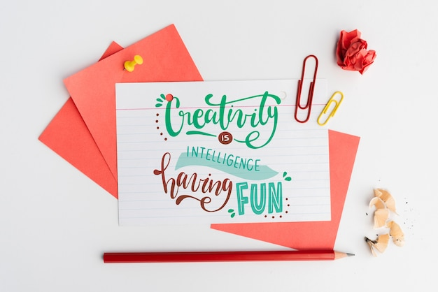 Creativity is intelligence having fun quote on white paper with stationery items