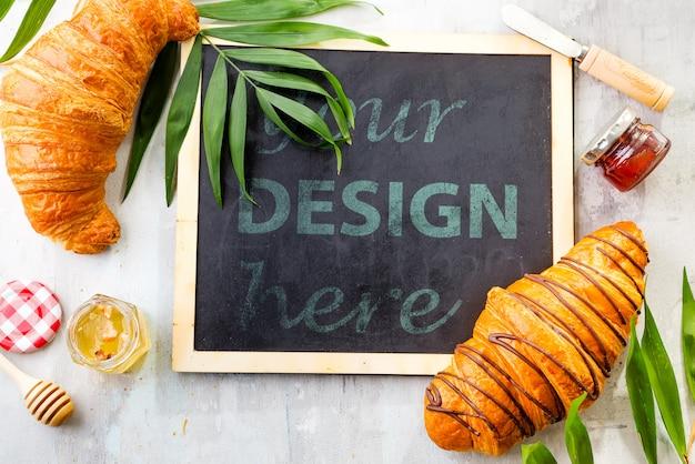 Круассан и джем с листьями пальмы, меловая доска, плоская планировка макета