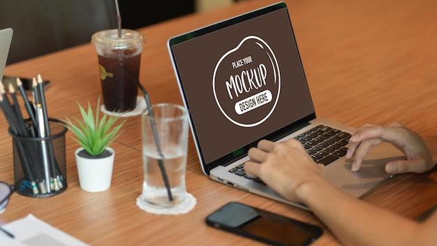 コーヒーの携帯電話でカフェの作業スペースでラップトップの空白の画面で作業している男性のクロップドショット