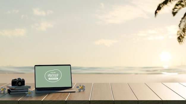 Cropped shot of blank screen mock up laptop computer with book and camera on wooden table with sea background Premium Psd