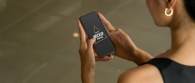 Cropped shot of female hands using mockup smartphone