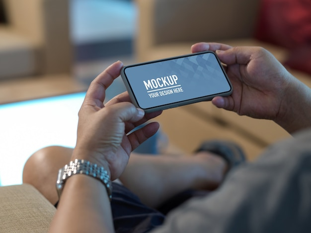 Cropped shot of male hands holding mock up horizontal smartphone while relaxed sitting on sofa