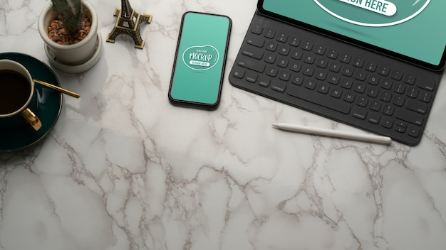 Cropped shot of marble table with mock up tablet, smartphone, coffee cup, decorations