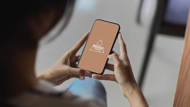 Обрезанный снимок девушки, использующей мобильный телефон с пустым экраном