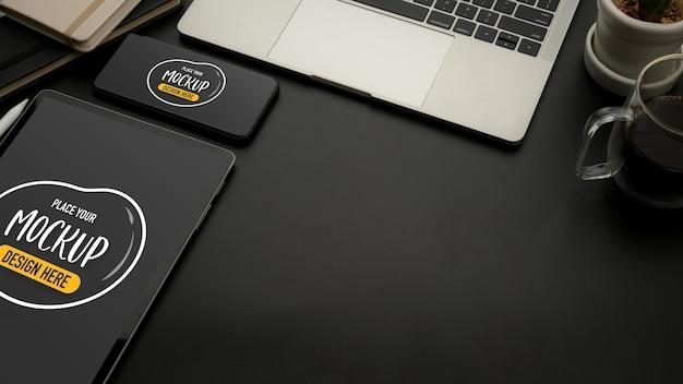 Обрезанный снимок черного офисного стола с макетом планшета, смартфона, ноутбука, принадлежностей и копией пространства