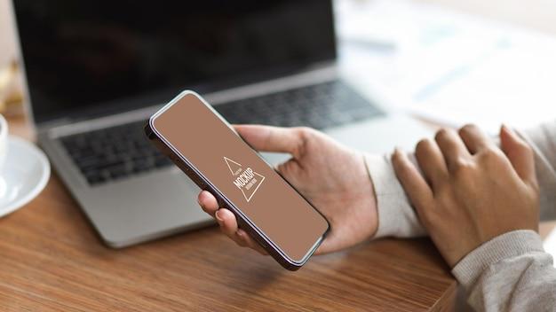 ノートパソコンと木製の机の上に空白の画面で携帯電話を保持しているビジネスマンのトリミングされたショット