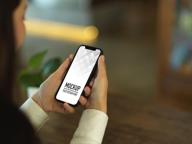 スマートフォンのモックアップを使用して実業家のクロップドショット