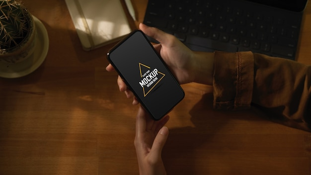 Обрезанный снимок женских рук, держащих макет смартфона на деревянном столе