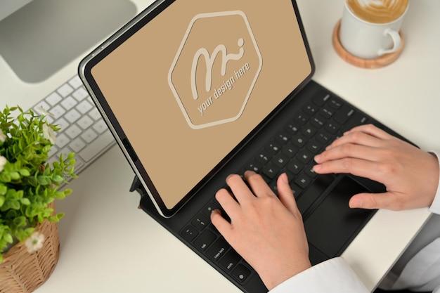태블릿 키보드에 입력하는 여성 손의 자른 샷