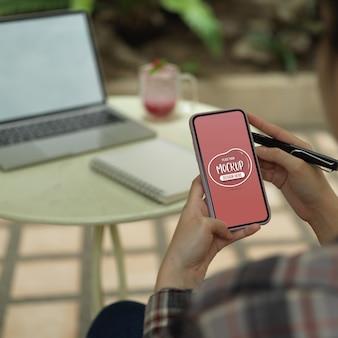 自宅の庭でオンラインで勉強しながらモックアップのスマートフォンを使用している女子学生の写真をトリミング
