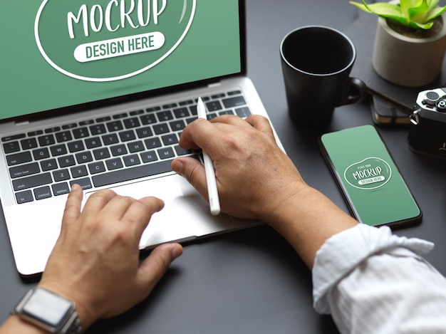 Обрезанный снимок мужских рук, печатающих на клавиатуре ноутбука с макетом смартфона на черном столе