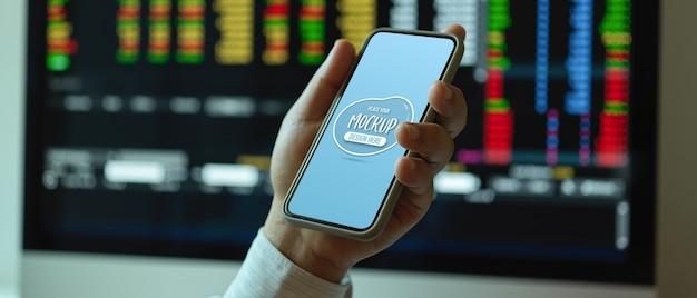 作業机に座っている間スマートフォンを模擬を持っている男性会社員の手のショットをトリミング