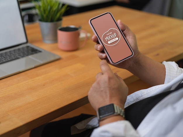 作業台に座ってスマートフォンのモックアップを使用して男性会社員のショットをトリミング