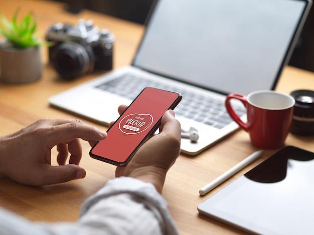 オフィスルームでラップトップ、カメラ、タブレットを操作しながらモックアップスマートフォンを使用して男性のクロップドショット