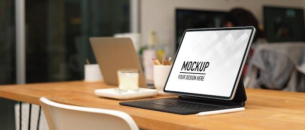 タブレットのモックアップとオフィスルームの事務用品と会議テーブルのトリミングされたショット