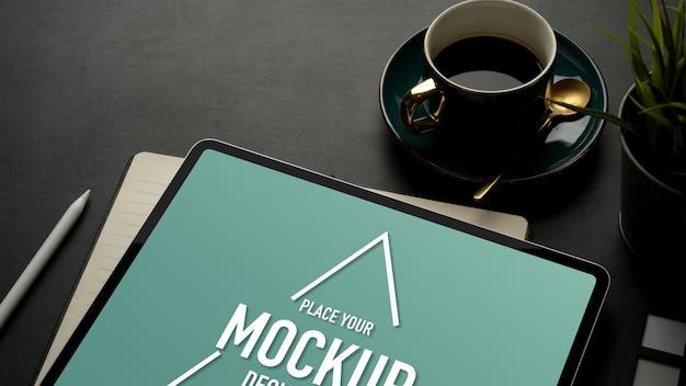 Обрезанный снимок макета цифрового планшета на черном столе с чашкой кофе