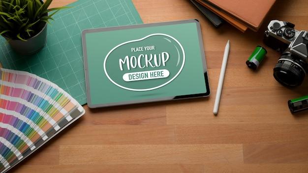 カメラ、消耗品、コピースペースを備えた木製のテーブルにデジタルタブレットのモックアップのクロップドショット