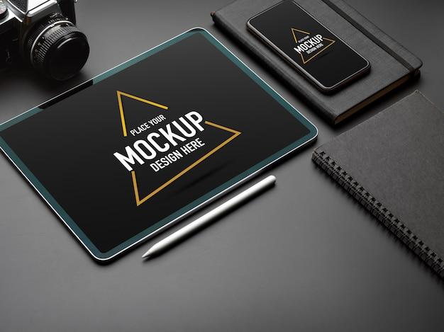 Обрезанный снимок макета цифрового планшета, смартфона и камеры на черном столе