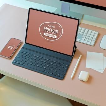 Обрезанный снимок макета цифрового планшета с клавиатурой на компьютерном столе в офисной комнате