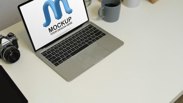 Обрезанный снимок рабочего места с копией пространства, макет ноутбука, камеры и принадлежностей на белом столе