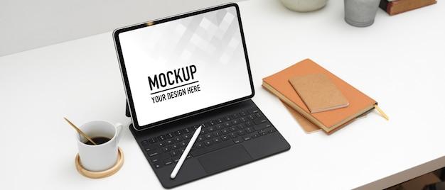 タブレットのモックアップとアクセサリーを備えたワークスペースのクロップドショット