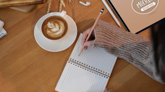 空白のノートブックに書く若い女性のショットをトリミング
