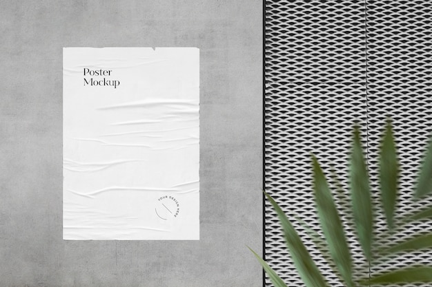 Crumpled poster mockup on the wall with greenery