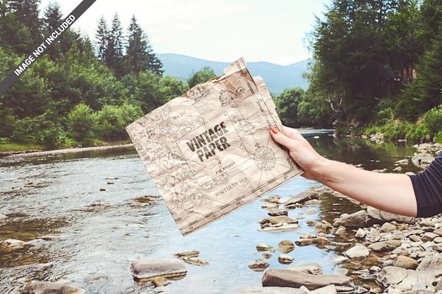 Crumpled vintage paper in hand adventure mockup