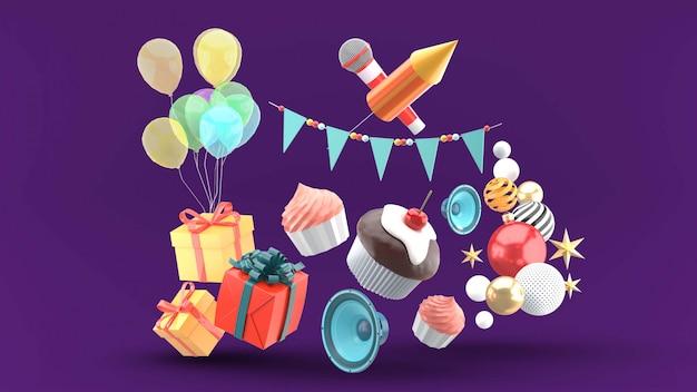 ギフトボックス、風船、スピーカー、ひもの旗に囲まれ、紫色に絞ったカップケーキ