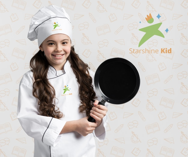 Cute chef holding cooking pan