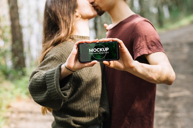 Милая пара на природе с макетом смартфона