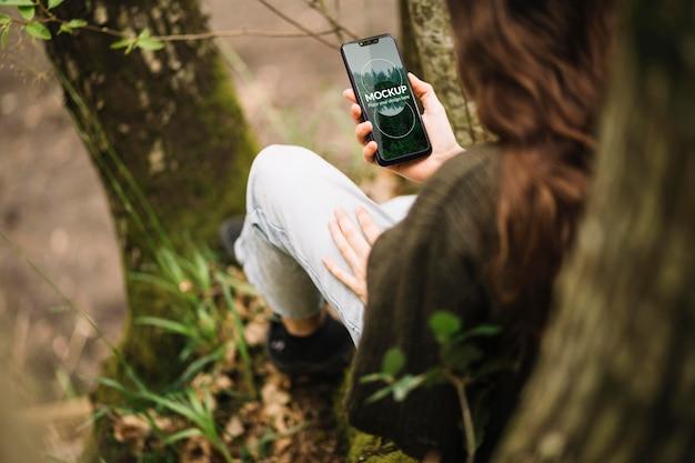 Милая женщина на природе с макетом смартфона