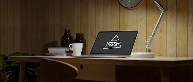 낮은 조명 아래 나무 작업대에 열린 노트북 테이블 램프 머그가 있는 어두운 가정 작업실