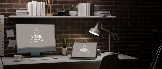 Dark working space in apartment with red brick wall blank laptop and tablet screen for your brand