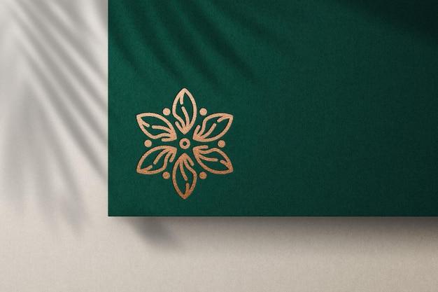 Debossed logo mockup with bronze foil on green paper
