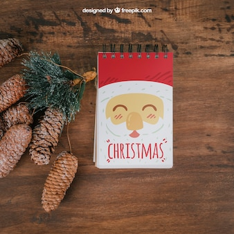 Decorative christmas mockup with notepad and pine cones