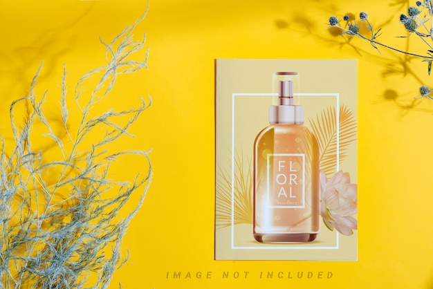 Decorative paper card mockup with bottle anddry plants