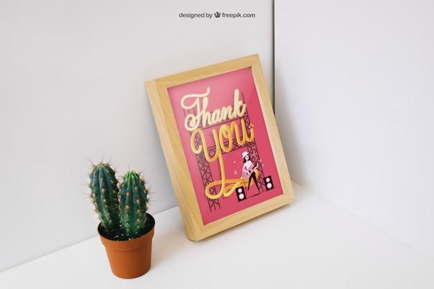 Decorative photo frame mockup with cactus