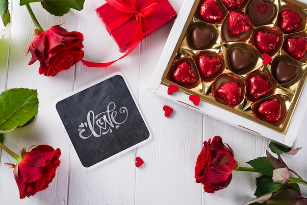 Delicious chocolate candies with gift boxes, roses and chalkboard mockup