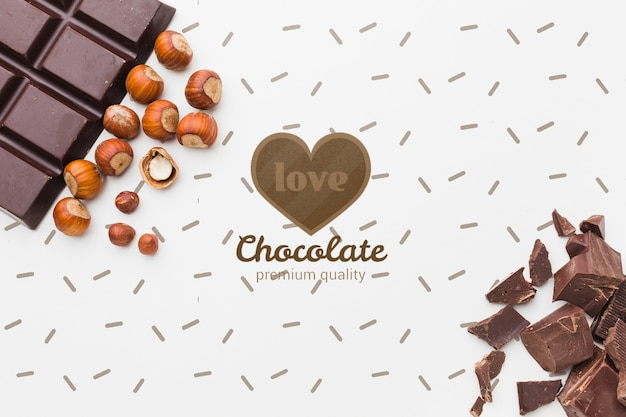 Delicious chocolate pieces and chestnuts on white background mock-up