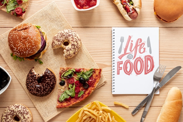 Delicious fast food on wooden table with notebook mock-up