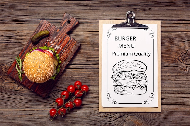 Delicious tomatoes and burger on wooden background