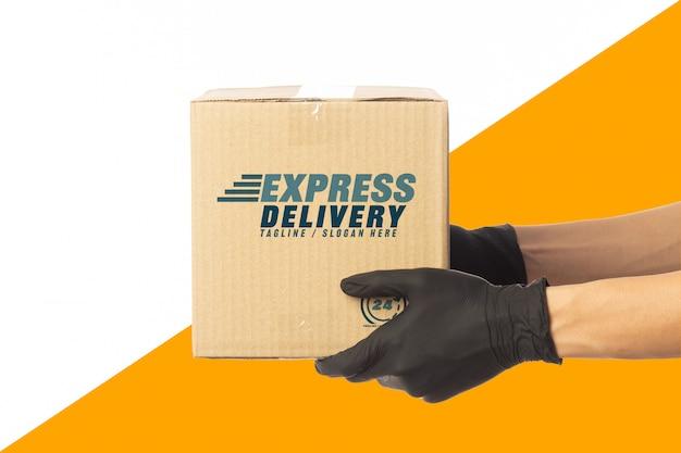 Рука работника доставляющего покупки на дом держа шаблон модель-макета картонных коробок для вашего дизайна. концепция службы доставки