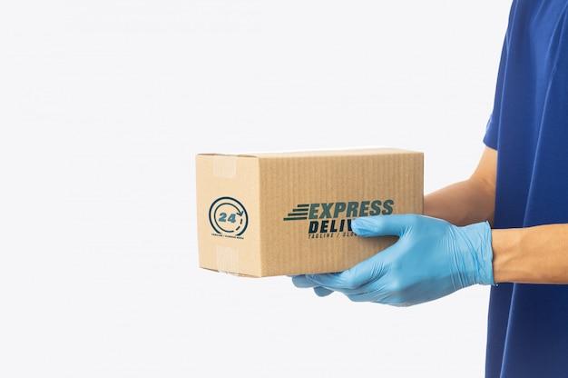 Рука работника доставляющего покупки на дом держа шаблон модель-макета картонных коробок для вашего дизайна.